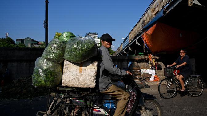 Seorang pedagang membawa sayuran di pasar grosir di Hanoi (26/8/2020). (AFP Photo/Manan Vatsyayana)