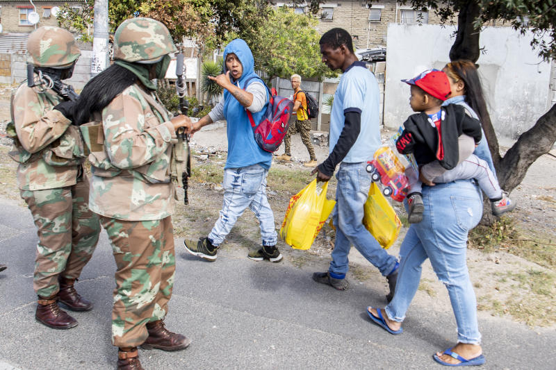 Soldiers interact with resident while on patrol in Mannenburg, Cape Town, South Africa Saturday, March 28, 2020. South Africa went into a nationwide lockdown to restrict public movements for 21 days in an effort to control the spread of the virulent COVID-19 coronavirus.(AP Photo)