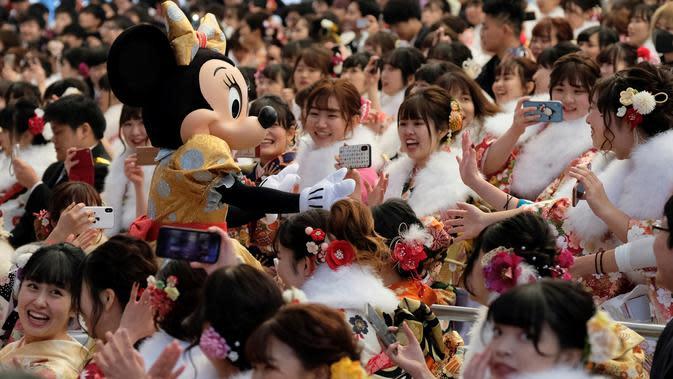 Tokoh Minnie Mouse menyambut para gadis dan pria pada perayaan Coming of Age Day atau Hari Kedewasaan di Tokyo Disneyland, di Urayasu, Senin (13/1/2020). Hari Kedewasaan adalah hari libur umum Jepang yang diadakan setiap hari Senin, minggu kedua di bulan Januari tiap tahunnya. (Kazuhiro NOGI/AFP)