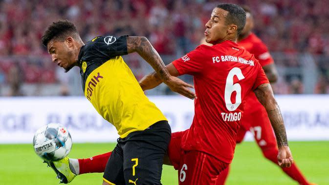 Gelandang Dortmund, Jadon Sancho, berebut bola dengan gelandang Bayern Munchen, Thiago Alcantara, pada laga Piala Super DFL di Stadion Signal Iduna, Dortmund, Sabtu (3/8). Dortmund menang 2-0 atas Munchen. (AFP/Ina Fassbender)