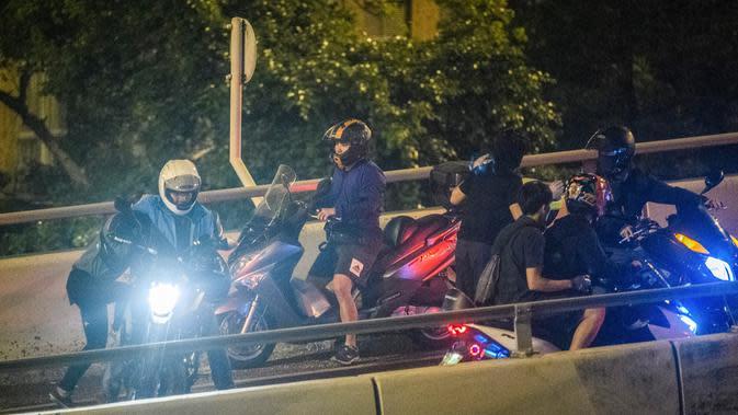 Demonstran dijemput menggunakan sepeda motor setelah menuruni jembatan menggunakan tali untuk melarikan diri dari Universitas Politeknik Hong Kong di Distrik Hung Hom, Hong Kong, Senin (18/11/2019). Lusinan demonstran berhasil melarikan diri dari kepungan polisi. (ANTHONY WALLACE/AFP)