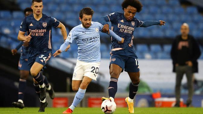 Penyerang Manchester City, Bernardo Silva, berebut bola dengan pemain Arsenal, Willian, pada laga Liga Inggris di Stadion Etihad, Minggu (18/10/2020). City menang dengan skor 1-0. (Martin Rickett/Pool via AP)