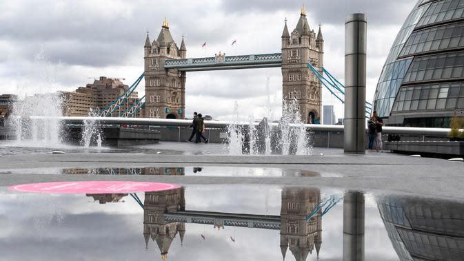 Orang-orang berjalan di depan Tower Bridge di London, Inggris, pada 6 Oktober 2020. Inggris melaporkan 14.542 kasus terkonfirmasi baru COVID-19, menambah total infeksi di negara itu menjadi 530.113, menurut data resmi yang dirilis pada Selasa (6/10). (Xinhua/Han Yan)