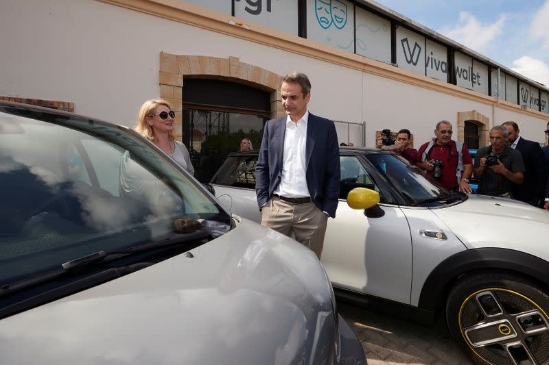 Greek Prime Minister Kyriakos Mitsotakis stands next to an electric car during an event about the country's low-carbon mobility plan, in Athens