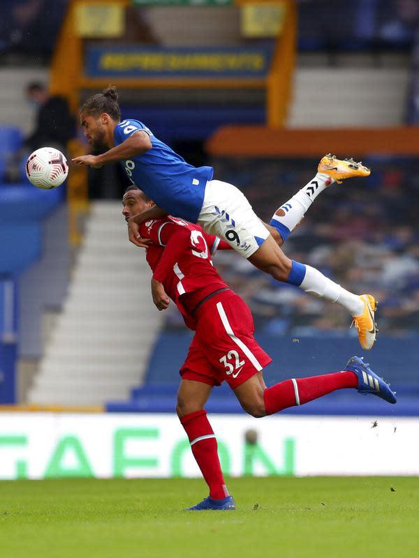 Pemain Everton Dominic Calvert-Lewin (atas) berebut bola dengan pemain Liverpool Joel Matip pada pertandingan Liga Premier Inggris di Stadion Goodison Park, Liverpool, Inggris, Sabtu (17/10/2020). Pertandingan berakhir dengan skor 2-2. (Cath Ivill/Pool via AP)