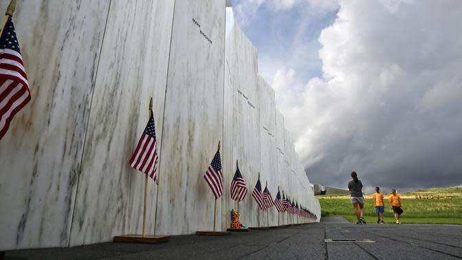 File foto 31 Mei 2018 ini, pengunjung di Peringatan Nasional Penerbangan 93 berhenti di Wall of Names untuk menghormati 40 penumpang dan anggota awak United Flight 93 yang tewas ketika jet yang dibajak itu jatuh di lokasi tersebut selama teroris 9/11. (AP Photo/Gene J. Puskar)