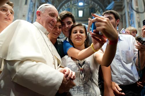 "FILE - In this file photo Wednesday, Aug. 28, 2013 Pope Francis has his picture taken inside St. Peter's Basilica with youths from the Italian Diocese of Piacenza and Bobbio who came to Rome for a pilgrimage, at the Vatican, Wednesday, Aug. 28, 2013. ""Selfie"" the smartphone self-portrait has been declared word of the year for 2013 by Britain's Oxford University Press. (AP Photo/L'Osservatore Romano, File)"