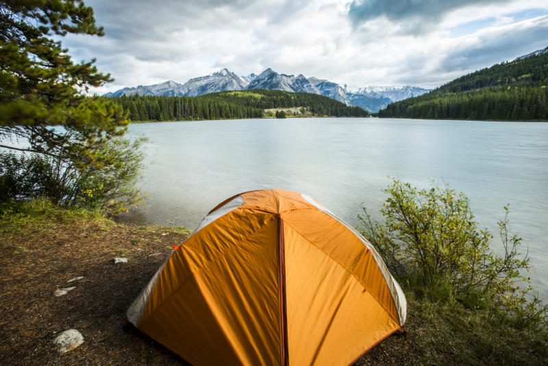 A stock image of a tent sitting at the edge of Tow Jacks Lake in Banff National Park, Canada.