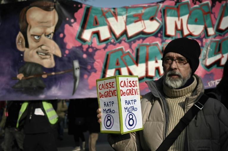 A protester holds a donation box for strikers in front of a banner portraying President Emmanuel Macron during a march against France's pension reform in Paris on Friday
