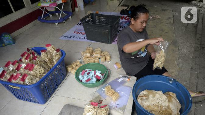 Pekerja mengemas jajanan tradisional kembang goyang di Kelurahan Karangan, Setu, Tangerang Selatan, Banten, Kamis (6/8/2020). Jajanan kue kering berbentuk bunga tersebut dijual dengan harga Rp 5 ribu per bungkus. (merdeka.com/Dwi Narwoko)