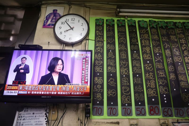 Taiwan President Tsai Ing-wen is seen on a TV screen during the third live policy address ahead of January's election, in Tainan