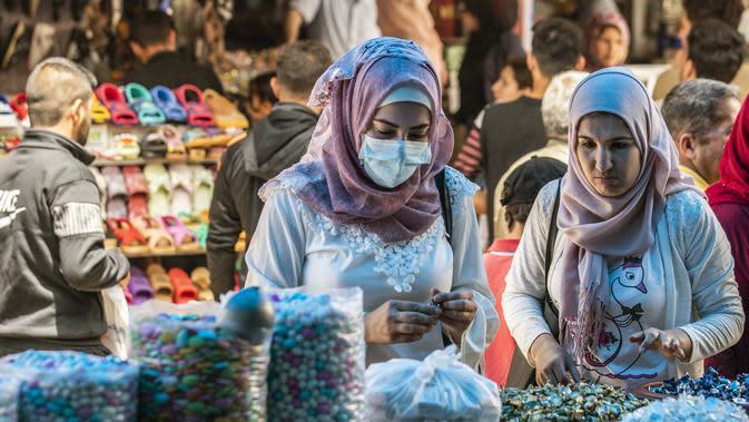 Para wanita berbelanja manisan menjelang Hari Raya Idul Fitri di pasar utama Kota Qamishli, Provinsi Hasakeh, Suriah, Selasa (19/5/2020). Hari Raya Idul Fitri menandai berakhirnya bulan suci Ramadan. (DELIL SOULEIMAN/AFP)