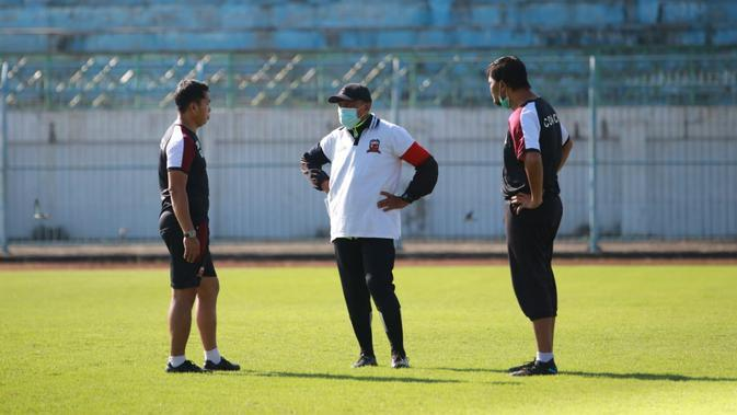 Pelatih Madura United, Rahmad Darmawan, tengah berdiskusi dengan tim kepelatihannya. (Bola.com/Permana Kusumadijaya)