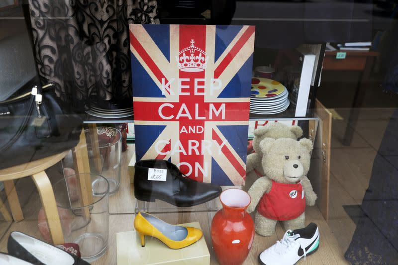 """FILE PHOTO: A """"Keep Calm and Carry On"""" sign is seen in the window of a closed charity store"""