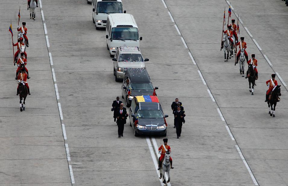 The hearse with the coffin containing the remains of Venezuela's late President Hugo Chavez makes its way from the Fort Tiuna military academy to his final resting place at a military museum  in Caracas, Venezuela,  Friday, March 15, 2013. Venezuelans lined up to bid their last farewell to Hugo Chavez on Friday. Chavez was 58 when he died of an undisclosed type of cancer on March 5. (AP Photo/Ariana Cubillos)