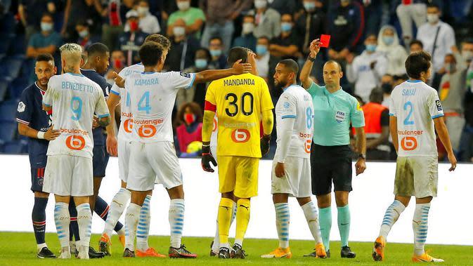 Wasit memberikan kartu merah saat pertandingan antara Paris Saint-Germain kontra Marseille pada laga Ligue 1 di di Stade de France, Senin (14/9/2020). PSG takluk 0-1 dari Marseille. (AP Photo/Michel Euler)