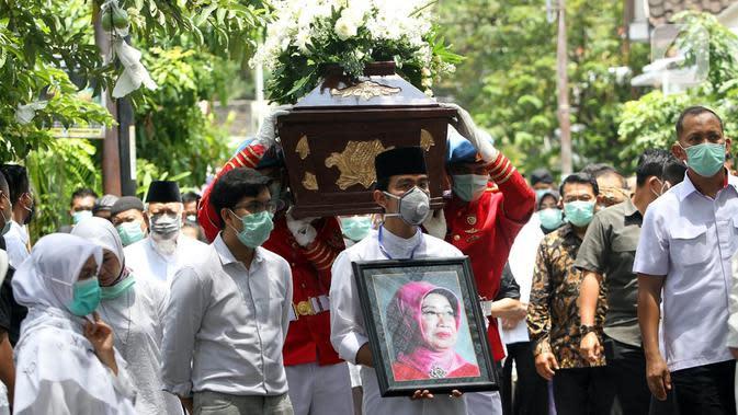 Putra Presiden Joko Widodo atau Jokowi, Gibran Rakabuming Raka (tengah) membawa foto sang nenek Sudjiatmi Notomihardjo saat akan disalatkan di masjid dekat kediamannya di Solo, Jawa Tengah, Kamis (26/3/2020). Sujiatmi Notomiharjo wafat di RST Slamet Riyadi, Solo. (Liputan6.com/Fajar Abrori)