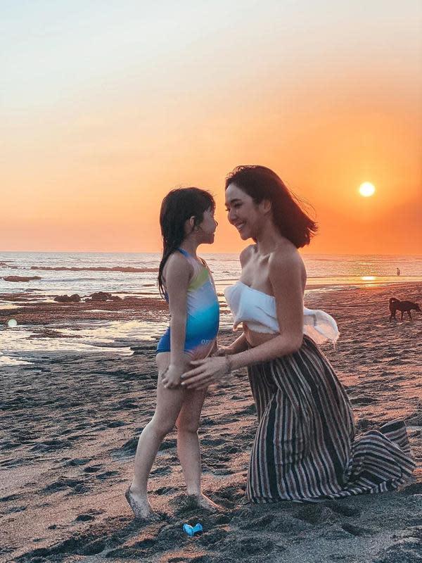 Selanjutnya adalah potret kebersamaan ibu dan anak ini saat berada di pantai. Pemandangannya sangat cantik di saat matahari hendak tenggelam. (Instagram/gisel_la)
