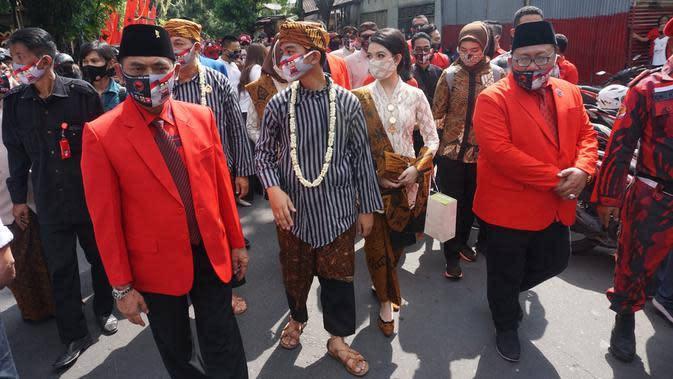 Calon Wali Kota-Wakil Wali Kota yang diusung PDIP Gibran Rakabuming Raka dan istrinya saat mendaftar ke KPU, Jumat (4/9/2020). (Liputan6.com/Fajar Abrori)