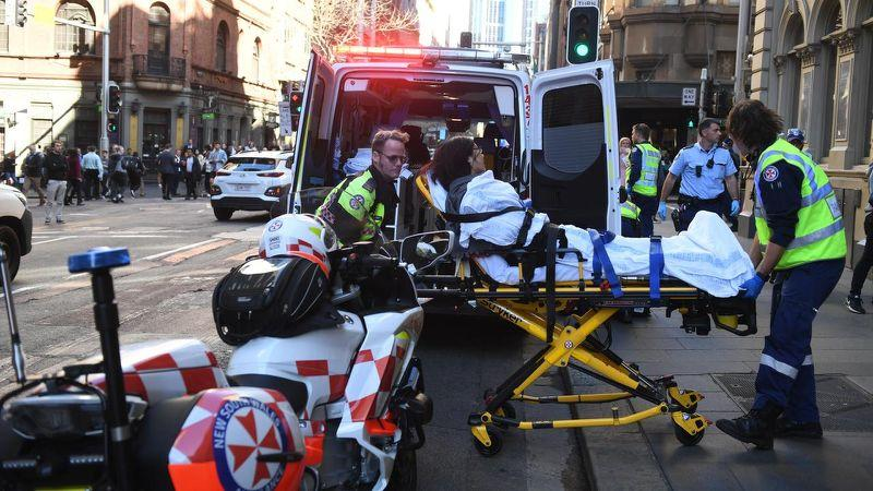 A women on a stretcher is taken by ambulance from Hotel CBD at the corner of King and York Street in Sydney.