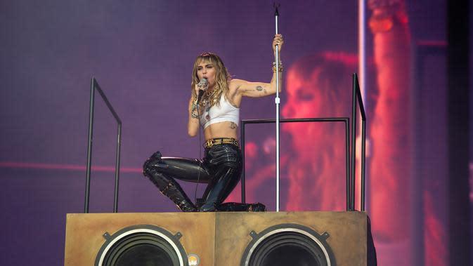 Aksi Miley Cyrus saat tampil pada hari terakhir Festival Glastonbury di Worthy Farm, Somerset, Inggris, Minggu (30/6/2019). Miley Cyrus tampil panas dengan gaya berapi-api saat menghibur ribuan penonton Festival Glastonbury. (OLI SCARFF/AFP)