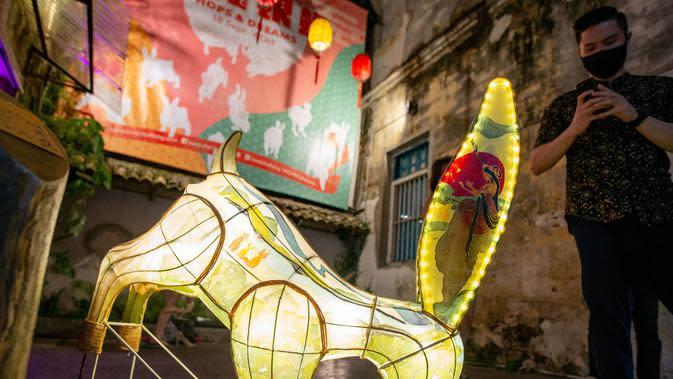 Seorang pria memotret instalasi Jade Rabbit di Kwai Chai Hong, Kuala Lumpur, Malaysia, 25 September 2020. Delapan desain unik instalasi seni Jade Rabbit dipamerkan di Kwai Chai Hong dalam sebuah acara untuk merayakan Festival Pertengahan Musim Gugur mendatang. (Xinhua/Chong Voon Chung)