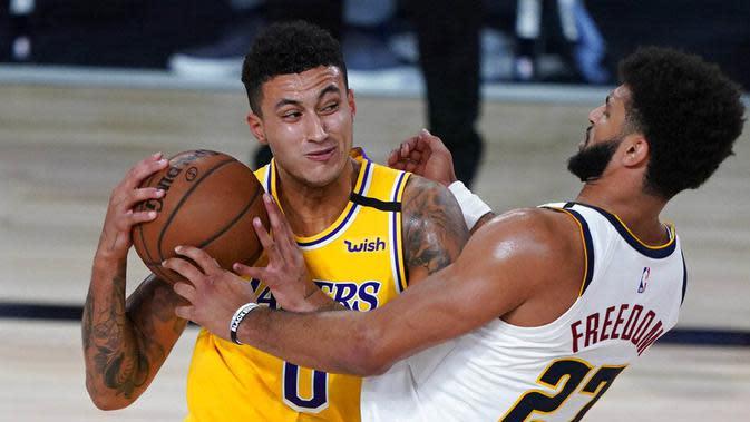 Pebasket Los Angeles Lakers, Kyle Kuzma, berusaha melewati pemain Denver Nuggets, Jamal Murray, pada laga NBA di The Arena, Senin (11/8/2020). LA Lakers menang dengan skor 124-121. (AP Photo/Ashley Landis, Pool)