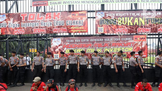 Polisi berjaga saat buruh yang tergabung dalam Gerakan Buruh Bersama Rakyat (Gebrak) berdemonstrasi di depan Gedung DPR, Jakarta, Senin (13/1/2020). Massa menyuarakan penolakan mereka terhadap Omnibus Law Rancangan Undang-Undang Cipta Lapangan Kerja. (Liputan6.con/Johan Tallo)