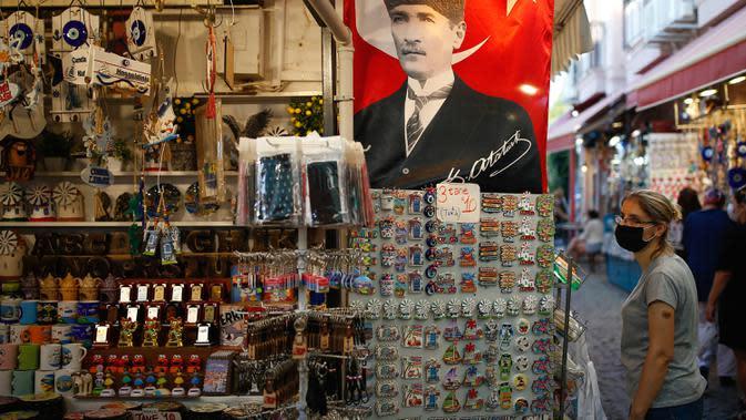 Poster pendiri Turki modern Mustafa Kemal Ataturk terlihat di sebuah toko, ketika turis yang mengenakan masker melintas di kota Ayvalik, Laut Aegea, Rabu (9/9/2020). Turki telah mewajibkan penggunaan masker di semua lokasi selain di rumah, menyusul lonjakan kasus COVID-19. (AP Photo/Emrah Gurel)