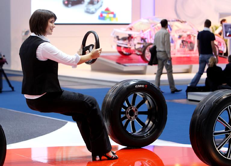 A woman seems to hover at a stand of a tire company at the 64th Frankfurt Auto Show in Frankfurt, Germany, Wednesday, Sept.14, 2011.(AP Photo/Michael Probst)