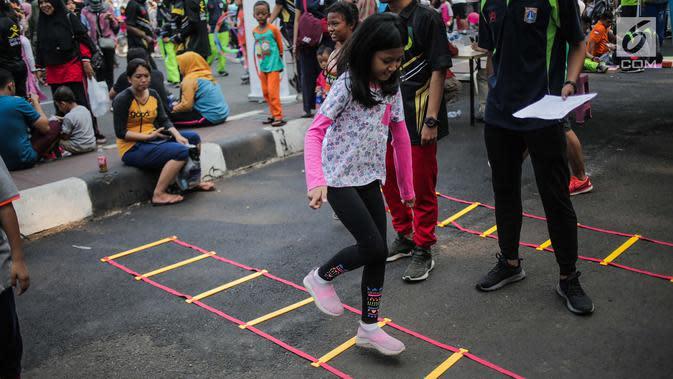 Anak-anak bermain permainan tradisional gobak sodor ditemani sejumlah mahasiswa dari Penggerak Olahraga saat car free day (CFD) di kawasan Bundaran HI, Jakarta, Minggu (14/7/2019). Kegiatan yang rutin digelar ini untuk mengajak masyarakat DKI Jakarta aktif berolahraga. (Liputan6.com/Faizal Fanani)