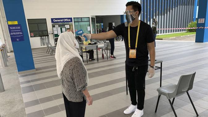 Petugas memeriksa suhu tubuh pemilih yang memberikan suara dalam pemilu di TPS Dunearn Secondary School, Singapura Jumat (10/7/2020). Pemilu di tengah pandemi COVID-19, warga Singapura memberikan suara mereka dengan mengenakan masker dan sarung tangan plastik. (AP Photo/Royston Chan)