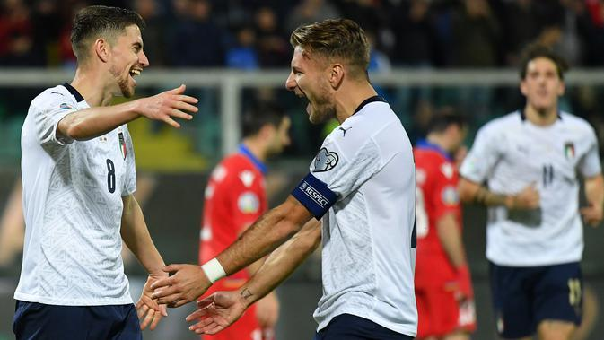 Gelandang Italia, Jorginho, merayakan gol yang dicetak Ciro Immobile ke gawang Armenia pada laga Kualifikasi Piala Eropa 2020 di Stadion Renzo Barbera, Palermo, Senin (18/11). Italia menang 9-1 atas Armenia. (AFP/Andreas Solaro)