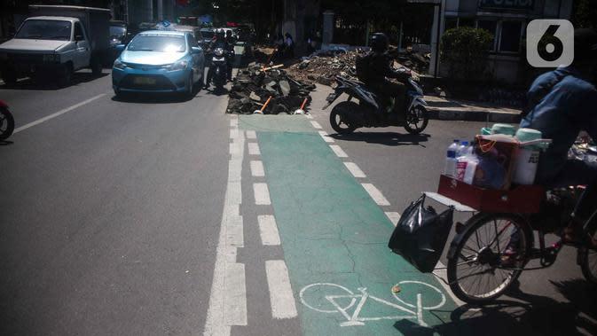 Pengguna jalan melintas di samping jalur sepeda yang di bongkar di kawasan Cikini, Jakarta, Selasa (19/11/2019). Jalur sepeda berumur 2 bulan tersebut dibongkar akibat proyek pelebaran trotoar. (Liputan6.com/Faizal Fanani)