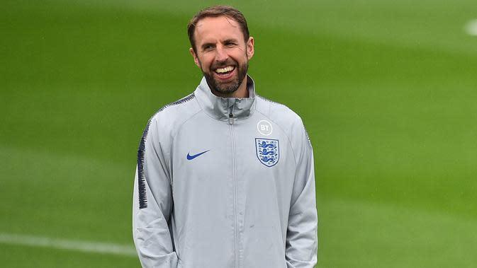 Pelatih Inggris, Gareth Southgate tersenyum saat melihat pemainnya berlatih di Staplewood Campus di southampton, Inggris selatan (9/9/2019). Inggris akan bertanding melawan Kosovo pada grup A Kualifikasi Euro 2020 di Stadion Saint Mary. (AFP Photo/Glyn Kirk)