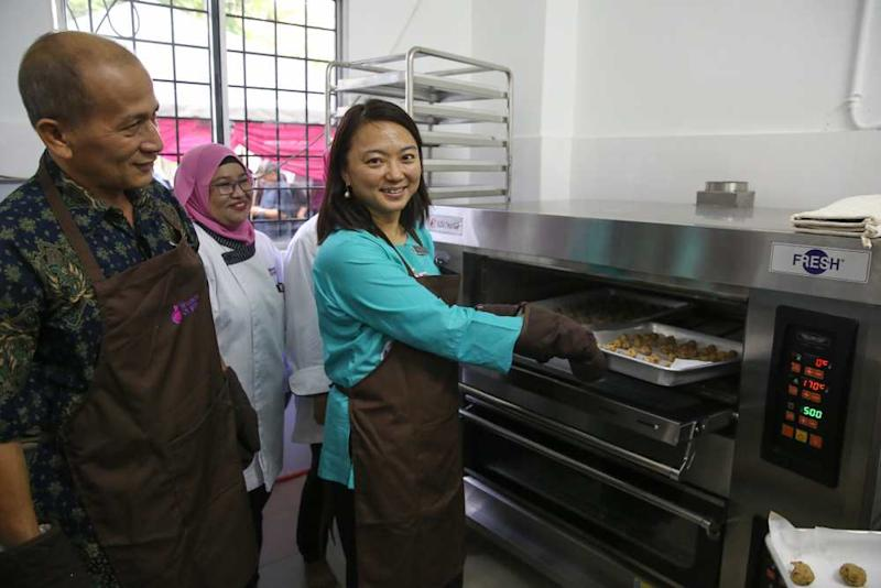 Hannah Yeoh puts a tray of cookies into the oven during the launch of the Women of Will's Community Kitchen in Kuala Lumpur May 25, 2019. ― Pictures by Yusof Mat Isa