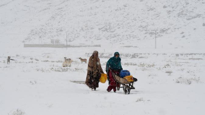 Dua wanita mengambil air minum saat hujan salju di Quetta, Pakistan, Minggu (12/1/2020). Sebanyak 54 orang dilaporkan tewas akibat cuaca buruk di Pakistan dan Afghanistan. (Banaras KHAN/AFP)