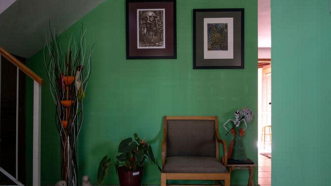 Sebuah kursi, tanaman, lukisan, dan sosok Catrina, semua milik Hebert Axel Gonzalez, sutradara teater yang meninggal karena COVID-19 pada April, kini menghiasi pintu masuk rumah rekannya Carlos Corro di Tijuana, Negara Bagian Baja California, Meksiko, 23 Juni 2020. (Guillermo ARIAS/AFP)