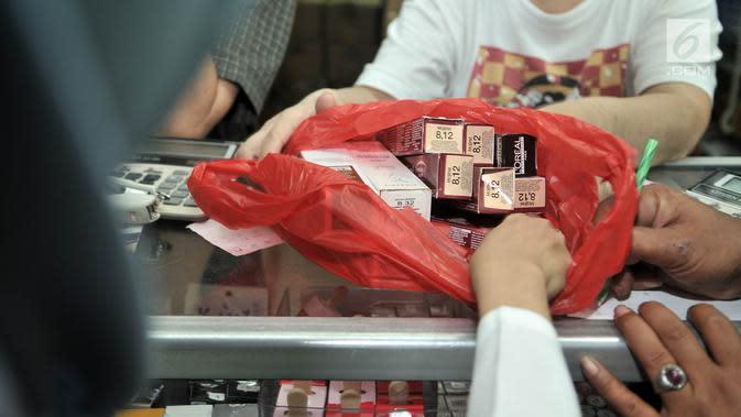Petugas menyita kosmetik saat melakukan razia di pertokoan Pasar Baru, Jakarta, Rabu (12/12). Razia BPOM bersama petugas Dinkes itu guna mencegah peredaran produk kosmetik yang tidak dilengkapi surat izin dan kedaluwarsa. (Merdeka.com/Iqbal S. Nugroho)