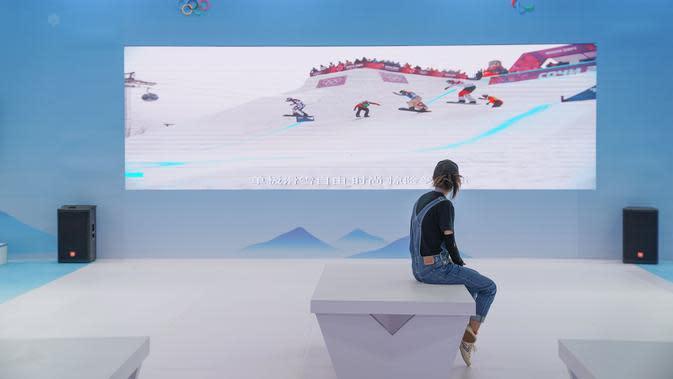 Seorang wanita menonton video promosi olahraga musim dingin di paviliun pameran outdoor di dekat China National Convention Center, lokasi penyelenggaraan Pameran CIFTIS), di Beijing Olympic Park di Beijing, China (1/9/2020). (Xinhua/Peng Ziyang)
