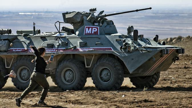 Seorang wanita Kurdi melemparkan batu ke kendaraan militer Turki di dekat kota Al-Muabbadah, bagian timur laut Hassakah, Suriah (8/11/2019). Pelemparan batu terjadi saat militer Turki melakukan konvoi dengan militer Rusia. (AFP/Delil Souleiman)