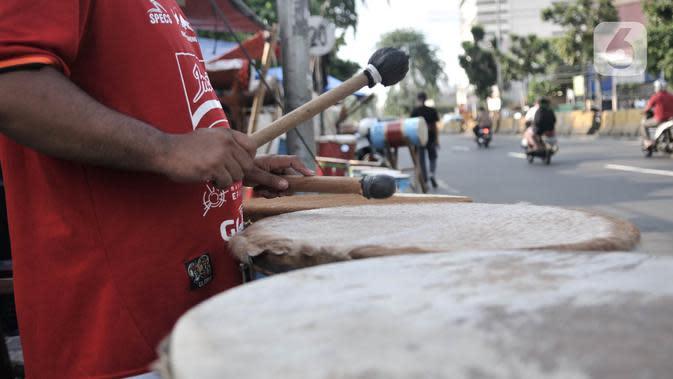Pedagang memukul beduk saat menunggu pembeli di kawasan Tanah Abang, Jakarta, Selasa (19/5/2020). Merebaknya pandemi virus corona Covid-19 di Ibu Kota menyebabkan omset penjualan beduk di Tanah Abang menurun hingga 70 persen. (merdeka.com/Iqbal Nugroho)
