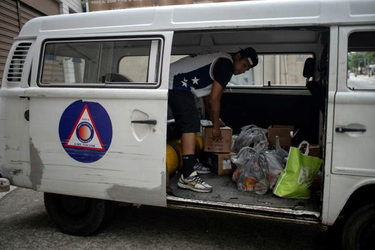 A volunteer loads a van with donations of basic food supplies for residents of the City of God favela -- one-quarter of Rio de Janeiro's residents live in such slums
