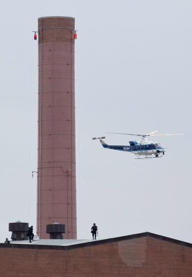A police helicopter flies overhead as police walk on the roof of a building as they respond to a shooting at the Washington Navy Yard in Washington