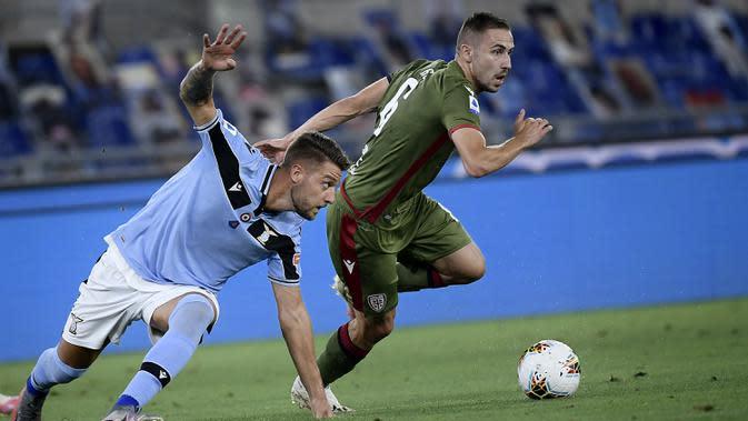 Gelandang Lazio, Luis Alberto, berebut bola dengan gelandang Cagliari, Artur Ionita, pada laga lanjutan Serie A pekan ke-35 di Stadio Olimpico, Jumat (24/7/2020) dini hari WIB. Lazio menang 2-1 atas Cagliari.(AFP/Filippo Monteforte)