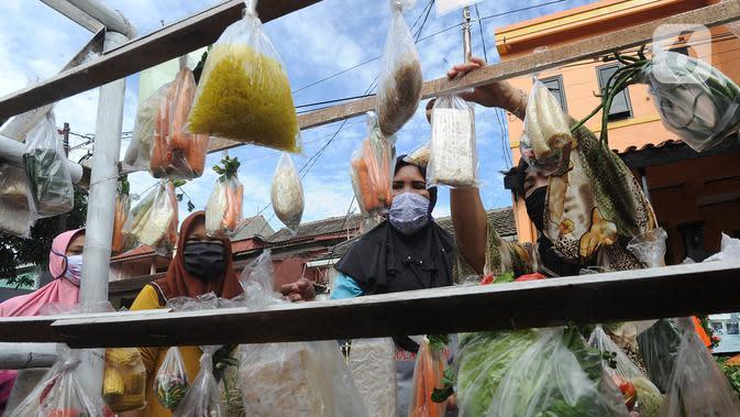Warga terdampak Covid-19 mengambil bahan pangan gratis di Kompleks Bumi Menteng Asri, Rt 01/18, Kelurahan Menteng, Bogor, Kamis (21/5/2020). Bahan pangan tersebut disediakan secara swadaya warga setempat dan sudah berjalan selama Bulan Ramadan. (merdeka.com/Arie Basuki)
