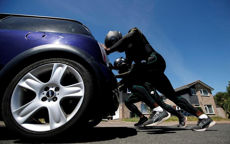 L/Cpl Stephens and Nimroy Turgott push a Mini Cooper around the streets of Peterborough for their training - REUTERS