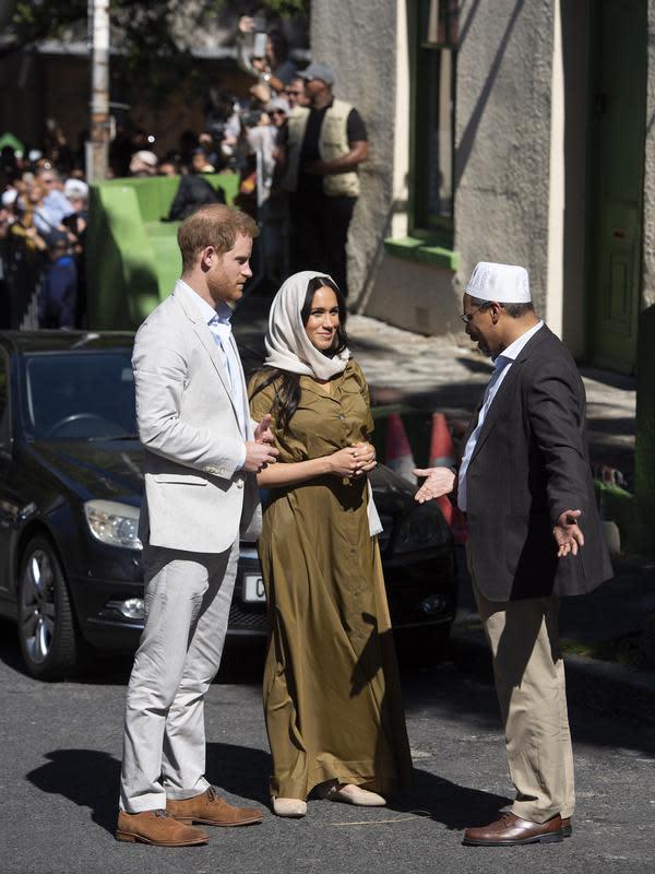 Duchess of Sussex Meghan Markle bersama suaminya, Pangeran Harry berbincang dengan seorang pria saat mengunjungi Masjid Auwal, Cape Town, Afrika Selatan (24/9/2019). (AFP Photo/David Harrison)