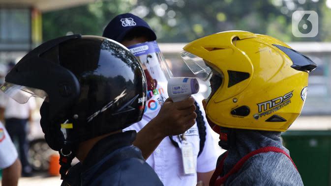 Petugas mengecek suhu pengunjung sebelum memasuki Taman Margasatwa Ragunan, Jakarta, Sabtu (20/6/2020). Ragunan mulai dibuka kembali untuk pengunjung di Sabtu ini pada masa PSBB transisi dengan pembatasan dan penerapan protokol kesehatan yang ketat. (Liputan6.com/Herman Zakharia)