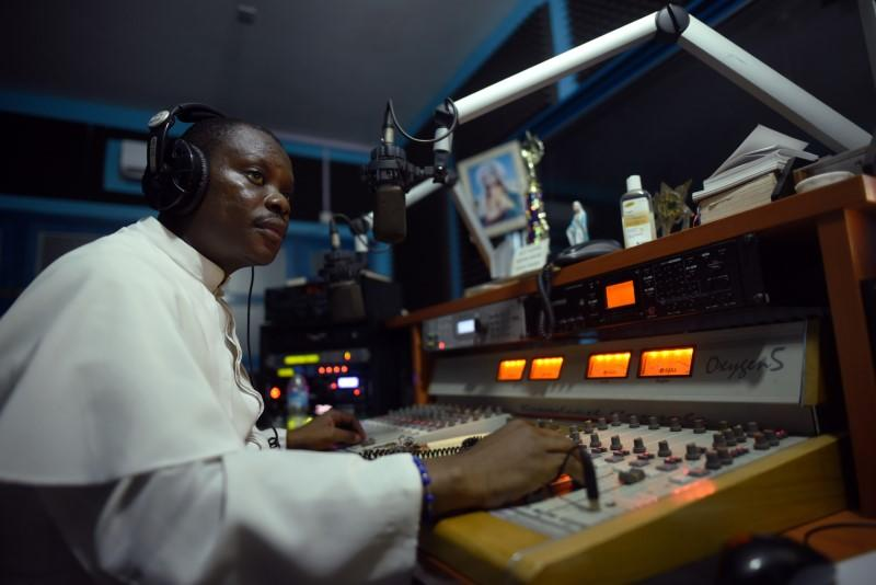 Reverend Father John Peter Bebeley sits behind the mixing table at Radio Maria, in Freetown